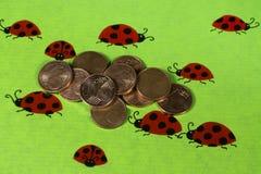 Поздравительная открытка с ladybirds и монетками цента Стоковое Изображение