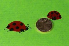 Поздравительная открытка с ladybirds и монетками цента Стоковое Изображение RF