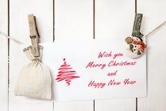 Поздравительная открытка holdingChristmas clothespines снеговика рождества Стоковое фото RF