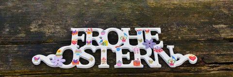 Поздравление счастливая пасха в немце Текст на деревянной деревенской предпосылке Стоковое фото RF