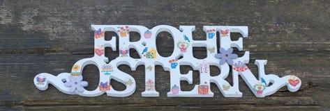 Поздравление счастливая пасха в немце Украшенные письма на деревянной деревенской предпосылке Стоковые Изображения