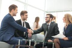 Поздравления! 2 жизнерадостных бизнесмена тряся руки пока Стоковое Изображение RF