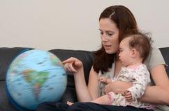 Поиск матери и младенца и рассматривать глобус Стоковое фото RF