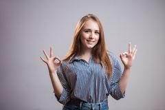 Поистине очаровательная рыжеволосая девушка при 2 руки показывая ОДОБРЕННЫЙ знак на серой предпосылке с космосом экземпляра для т стоковая фотография rf