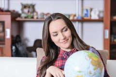 Пойдите на приключение Женщина мечтая о путешествовать по всему миру, смотрящ глобус в комнате дома Милое исследование девушки Стоковое Изображение