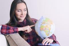 Пойдите на приключение Женщина мечтая о путешествовать по всему миру, смотрящ глобус в комнате дома Милое исследование девушки Стоковые Изображения