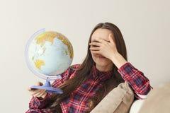Пойдите на приключение Женщина потехи мечтая о путешествовать по всему миру, переплетенный глобусу и закрывает глаза Счастливое м Стоковая Фотография