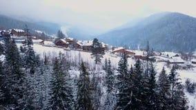 Показывая антенна обитаемого в местообитания в горах на зиме Здания горного села на снежных наклонах холма видеоматериал