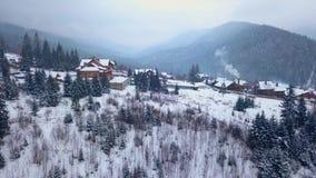 Показывая антенна обитаемого в местообитания в горах на зиме Здания горного села на снежных наклонах холма акции видеоматериалы