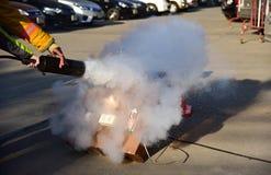 Показ инструктора как использовать огнетушитель на тренировке Стоковое Изображение