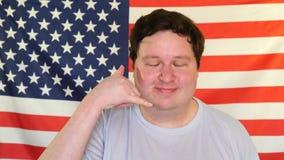 Показ молодого человека вызывает меня жестом на предпосылке флага США сток-видео