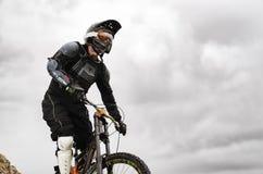 Покатый всадник на горном велосипеде в горном велосипеде едет вдоль дороги в природе против фона горы Стоковые Изображения