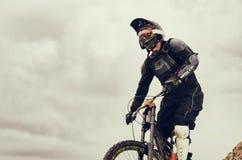 Покатый всадник на горном велосипеде в горном велосипеде едет вдоль дороги в природе против фона горы Стоковые Фото