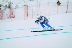 Покатый спортсмен маленькой девочки катаясь на лыжах к чашке конкуренции русской в горных лыжах Стоковое фото RF