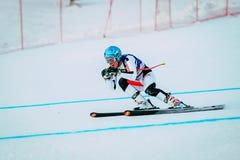 Покатый спортсмен молодого человека катаясь на лыжах к чашке конкуренции русской в горных лыжах Стоковое фото RF
