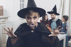 Пока его родственники подготавливают на хеллоуин, мальчик одевал в костюме ужасного порочного вампира Стоковые Фотографии RF
