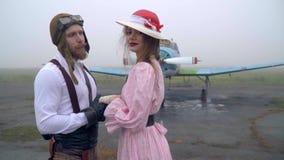 Пока женщина в розовом платье смотрит в камеру мужской пилот в влюбленности смотря женщину, стрельбу слайдера акции видеоматериалы