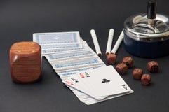 Покер тузов и деревянной кости с ashtray и сигаретами на a Стоковые Изображения RF