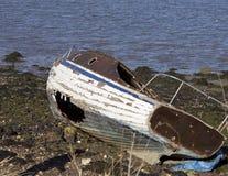 Покинутая и приставанная к берегу шлюпка с поврежденным корпусом Стоковая Фотография