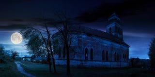 Покинутая католическая церковь на холме на ноче стоковые изображения