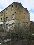 Покинутая покинутая промышленная мельница в huddersfield Англии с всходить на борт вверх и сломанных окнах Стоковое Изображение RF