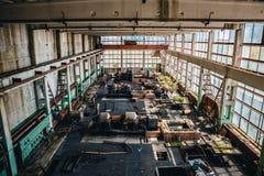 Покинутая промышленная внутренняя, большая мастерская с большими окнами и ржавые железные машины или инструменты металла Стоковые Фотографии RF