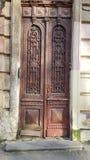 Покинутая старая красная дверь с поцарапанными деревянными панелями и богато украшенными решетками стоковые изображения