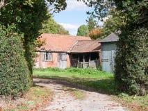 Покинутая старая несенный вниз с загородного дома фермы снаружи через изгородь Стоковые Изображения RF