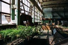 Покинутая фабрика внутрь, большие окна, ржавое стальное оборудование Стоковое фото RF