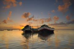 Покинутая шлюпка во время красивого восхода солнца Стоковые Фото