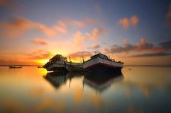 Покинутая шлюпка во время красивого восхода солнца Стоковая Фотография