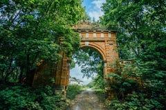 Покинутое и перерастанное ворот красного кирпича к бывшему поместью ` s Muromtsev в зоне Lipetsk стоковая фотография