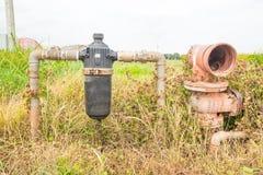 Покинутые деревенские труба водопровода и водяной фильтр в поле стоковое фото rf