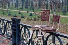 Покинутые стулья сваренные к стали утюжат загородку, абстрактную предпосылку Стоковые Изображения