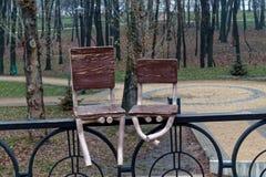 Покинутые стулья сваренные к стали утюжат загородку, абстрактную предпосылку Стоковое Изображение