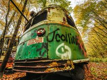Покинутый автомобиль вагонетки в древесинах в знаке падения с осторожностью Стоковое Изображение RF
