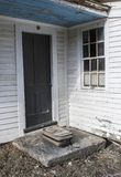 Покинутый дом с старым чемоданом на шаге стоковые изображения