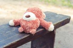 Покинутый на игрушке плюшевого медвежонка деревянной скамьи сиротливой Стоковая Фотография RF