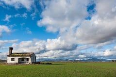 Покинутый дом в зеленом поле травы и облачного неба Стоковое Изображение