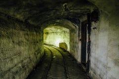 Покинутый тоннель перехода боеприпасов военного корабля с остатками железной дороги узкой колеи Стоковые Фотографии RF