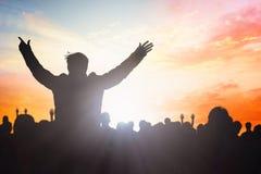 Поклонение верующих и чествует концепцию пасхи: группа в составе бог людей силуэтов поклоняясь на предпосылке неба захода солнца стоковое изображение rf