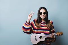 Поколение z женское с гавайской гитарой и знаком мира стоковые изображения rf