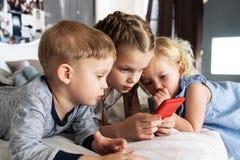 Поколение ZD: Дети лежат на кровати и взгляде в красный смартфон более старой девушки стоковые фотографии rf