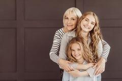3 поколения счастливых женщин смотря камеру стоковое изображение