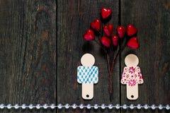 2 покрасили деревянного маленького человека и ветви с сердцами Стоковая Фотография