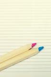 2 покрасили пинк и голубые деревянные карандаши на белой бумаге Стоковые Фотографии RF