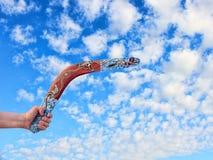 Покрасьте австралийский бумеранг в руке людей против пасмурной сини sk Стоковые Фотографии RF