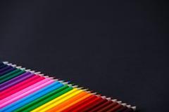 Покрасьте деревянные яркие карандаши тени выстраивают в ряд на темной предпосылке Стоковая Фотография RF
