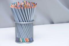 Покрасьте карандаши в busket на деревянной белой таблице с серой предпосылкой стоковые фото