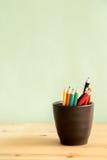 Покрасьте карандаши в коричневой керамической чашке на таблице стоковые изображения rf